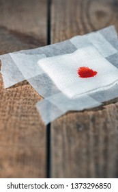 Used bandage with blood on wooden floor.