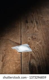 Used bandage fallen on wooden floor in strip of light.