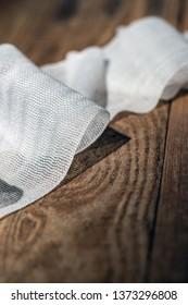 Used bandage gauze fallen on wooden floor.