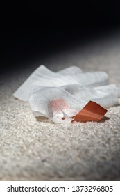 Used bandage with tape fallen on white carpet.