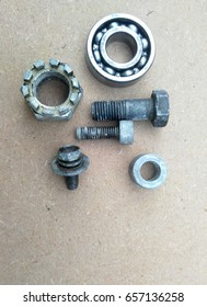 Used bearings, gaskets, screws and some other mechanical components of engines isolated on the high-pressure timber board.