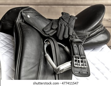 Used black dressage horse riding saddle with girth, stirrup and riding gloves on white saddle pad