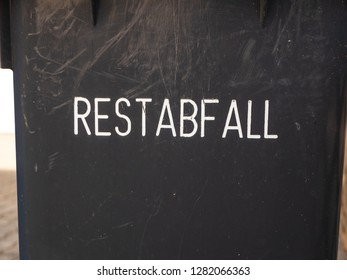 """used black Garbage can with the German word """"Restabfall"""" (residual waste)"""