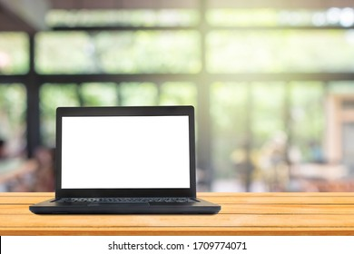 Used black laptop with blank white screen on wooden table and blurry image of coffee shop or cafe restaurant in background.