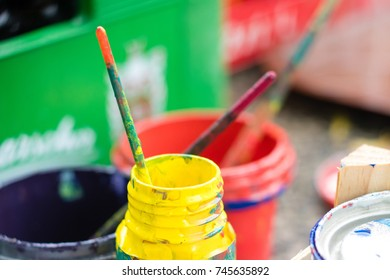 Used brushes and paint cans, red and yellow