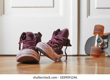 Used canvas shoes and skateboard on the floor