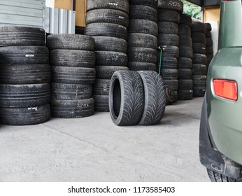 Used car tires stacked in piles at tire fitting service. Old wheels. Wheels for repair shop. Car service concept