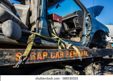 Used car transported to car recycle facility via flat deck truck by scrap car removal company.