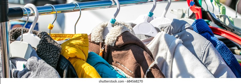 used child and baby winter clothes, jackets and coats displayed on rack at outdoor garage sale for shopping, reusing, exchanging, recycling or donating