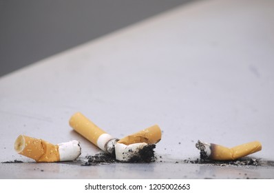 Used cigarettes and ash discarded on metal surface.
