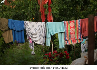 Used clothes washing dries on a rope in the yard.