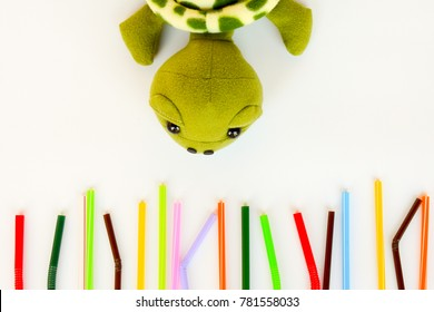 Used colorful plastic straws with turtle doll on white background, explaining the pollution is killing marine animals. Pollution concept. Ban single use plastic.