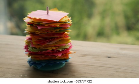 Used colorful post-it notes stack in stick white pike, put on the wooden table work space with background of green nature