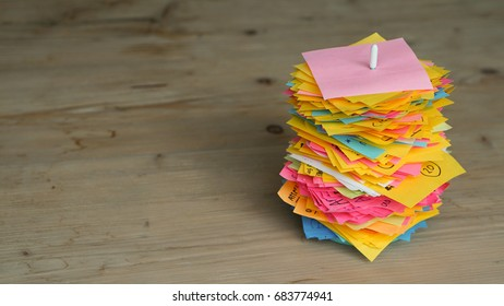 Used colorful post-it notes stack in stick white pike, put on the wooden table work space