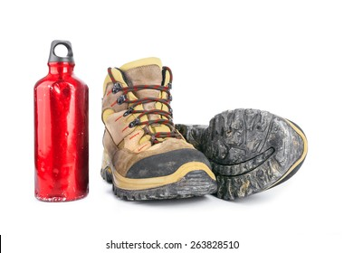 Used Dirty hiking boots and old battered red water bottle isolated on white background.