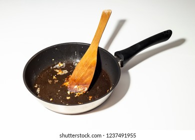 Used dirty iron black frying pan with stick food with wooden spoon in - close up on white background