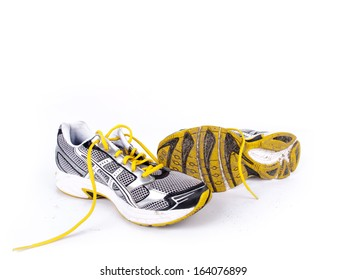 Used dirty pair of running shoes over a white background