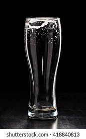 USED EMPTY Beer Glass with DROPS on black. FRESH! MUCH FOAM! Beer bubbles closeup. DRAFT. Overflow beer glass. Glass of alcohol. Closeup Cold Beer. Pint of beer. Good for brewery commercial
