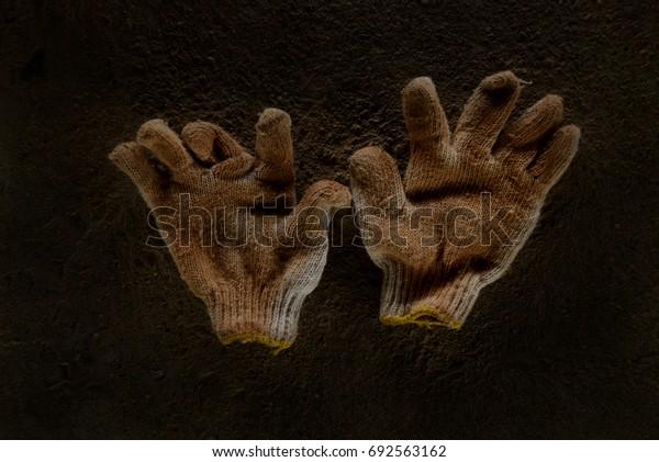 Used fabric gloves on dark cement floor.