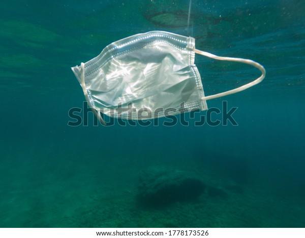 Used face mask floating in the sea, mediterranean sea. Catalonia, Spain. Covid-19 pollution. Coronavirus prevention risks