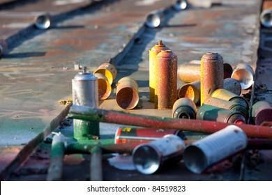 Used graffiti spray cans lay around