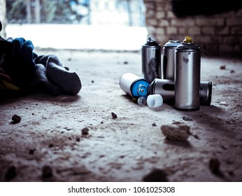 used graffiti spray paint cans on the ground
