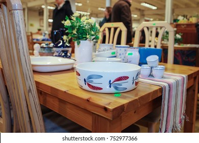 Used household items are sold in a thrift store. Shoppers are out of focus in the background.