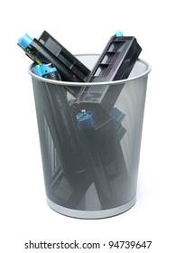 Used laser printer cartridges in metal trash bin over white