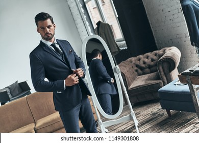 Used to look perfect. Handsome young man in full suit looking away and adjusting his jacket while standing indoors