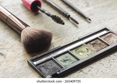 Used makeup kit on distressed wooden surface for beauty and cosmetics themed background