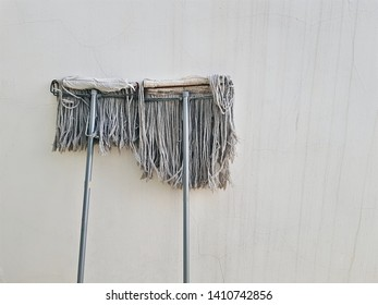 Used Mops for Housekeeping Lean Against Old Dirty Wall