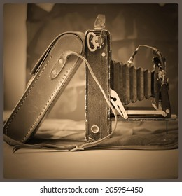 Used and old photographic camera on a sepia vintage still.