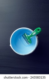 Used paintbrush in a paint bucket over dark background, above view