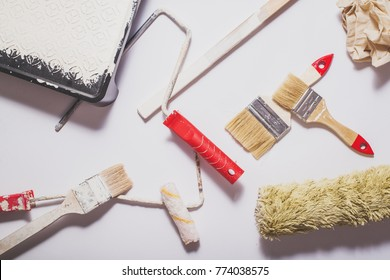 Used painting tools with red handles covered in warm white paint layed out in a composition on a plain white background