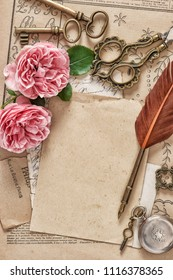 Used paper, antique feather pen, pink rose flowers. Vintage flat lay