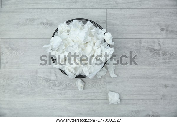 Used paper tissues in trash can on wooden floor, flat lay