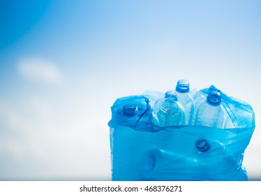 Used plastic bottles in a plastic bag with blue sky background