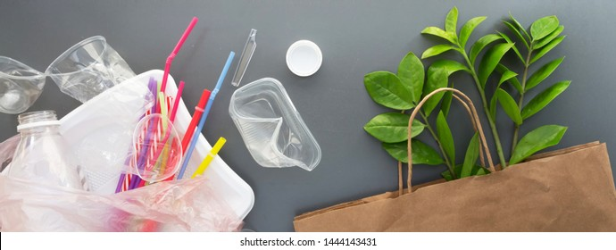 Used plastic bottles, glasses, cutlery and bags for recycling, the concept of recycling waste, ecology, land pollution on a gray background