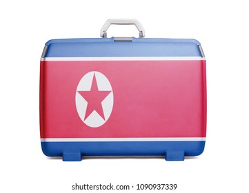 Used plastic suitcase with stains and scratches, printed with flag, North Korea