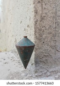 used plumb bob on cement wall background. Blurred background