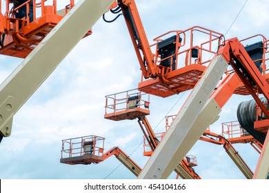 The Used Red Boom Lifts with the blue sky background in the warehouse for sale