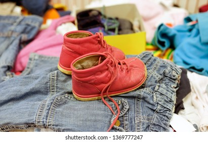 Used red shoes for children in a thrift shop between other used clothes - selective focus