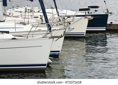 Used sail boats or yachts in a row for sale in a marina which buys and sells sailing equipment.
