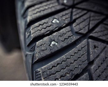 Used snow tire with metal studs close up. Protector of worn winter studded tire - wheel service. Lost studs. Old tires cause road accidents
