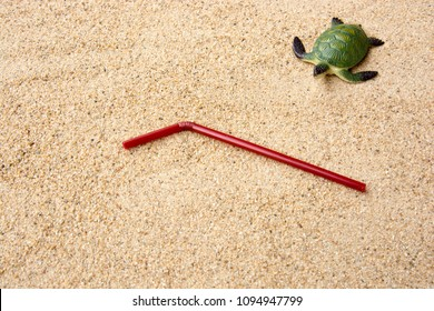 Used straw left on sandy beach background. Plastic pollution affecting marine ecology. Environment concept. Ban single use plastic. Top view with copy space.