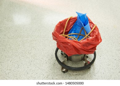 A used suction tube in red garbage bin on operating room floor