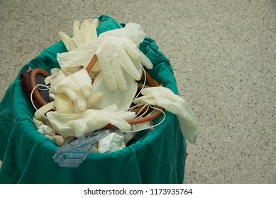 Used surgical gloves, gauzes with blood-stained, suction tube, plastic bag in garbage bin for biohazard disposal