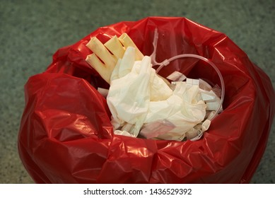 Used surgical gloves, tubing in a red garbage bin for biohazard disposal
