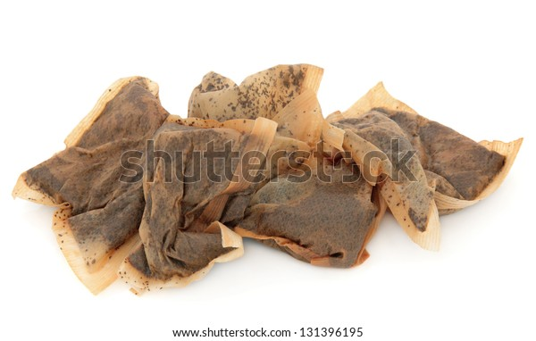 Used tea bag pile over white background.