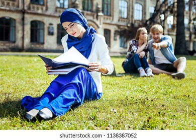Used to that already. Charming Muslim girl enjoying the day and reading her notes with a smile on a face while two bad mannered mates laughing at her in the background.